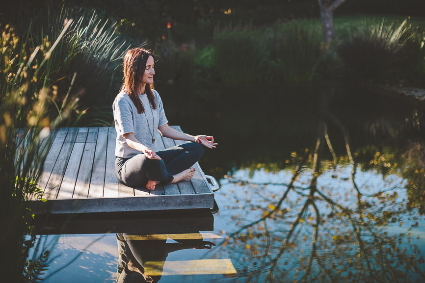 Young Woman Meditating On Wooden Deck At Waters Edge