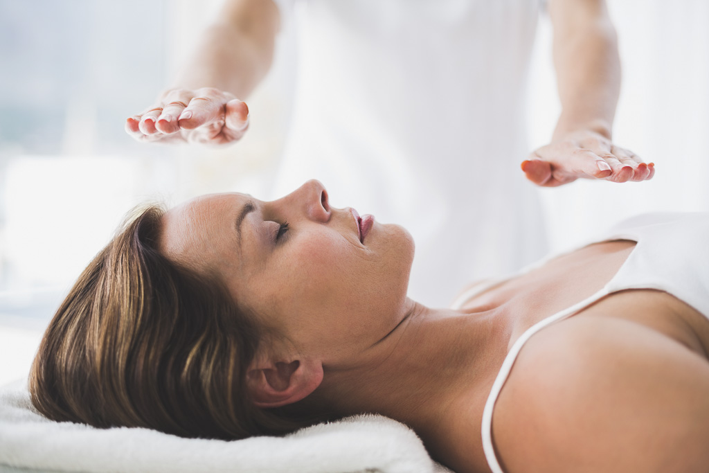 Midsection of therapist performing reiki treatment on woman at spa