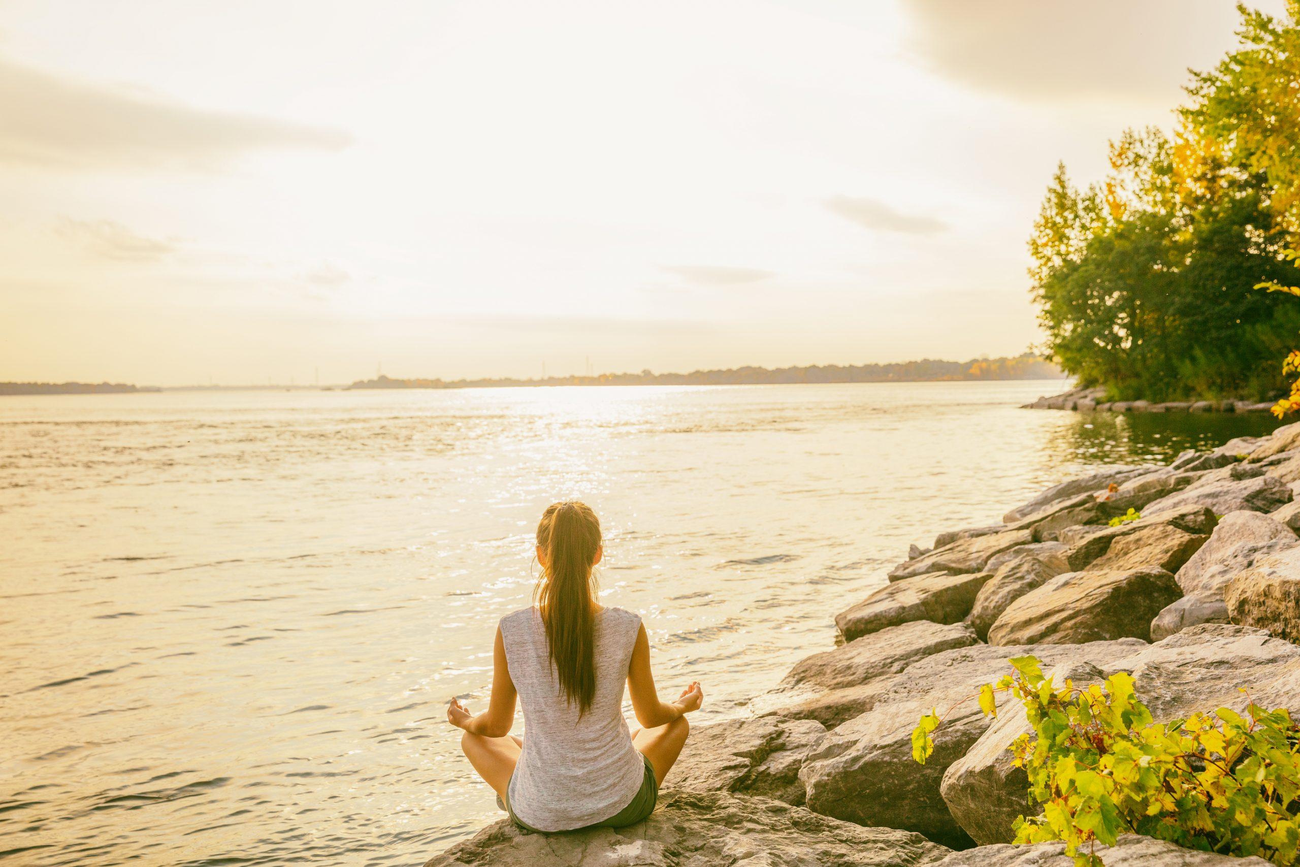 Woman meditating at the edge of a lake