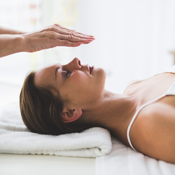 Therapist performing reiki on young woman's head